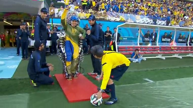 Exibição do exoesqueleto na abertura da Copa. Um juiz segura agachado uma bola que será chutada por pessoa utilizando o exoesqueleto.